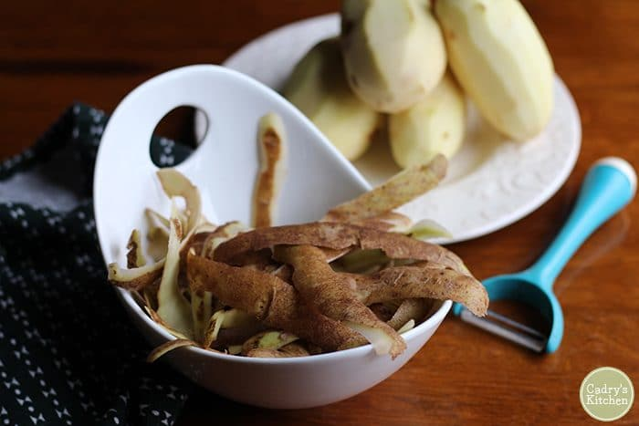 Potato peels in a bowl, peeled potatoes in background.