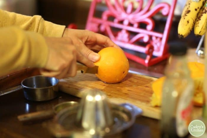 Orange getting sliced in half, maple syrup and juicer in foreground.