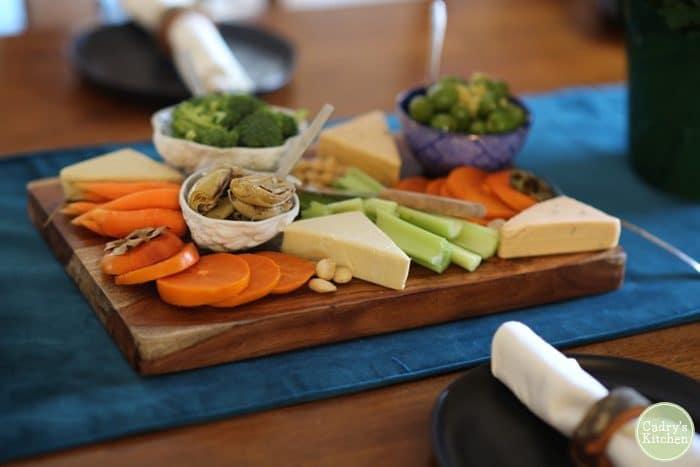 Vegan cheeseboard with persimmons, broccoli, carrots, celery, Marcona almonds, and Castelvetrano olives.