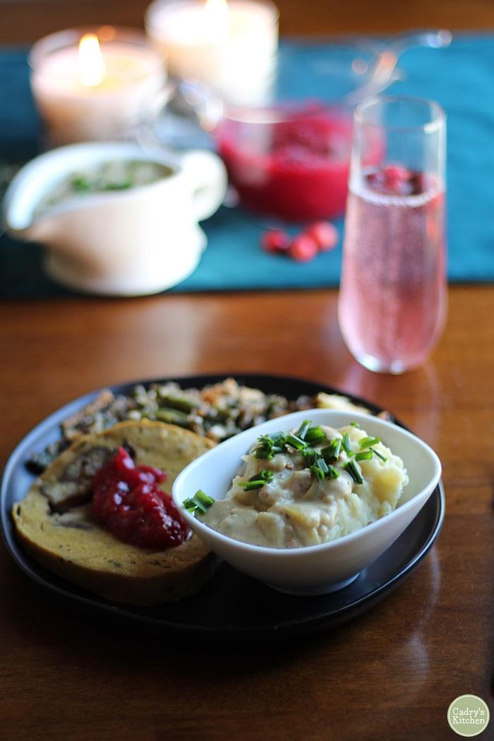 Mashed potatoes & seitan bacon vegan gravy on plate with Herbivorous Butcher seitan & Christmas dinner side dishes.