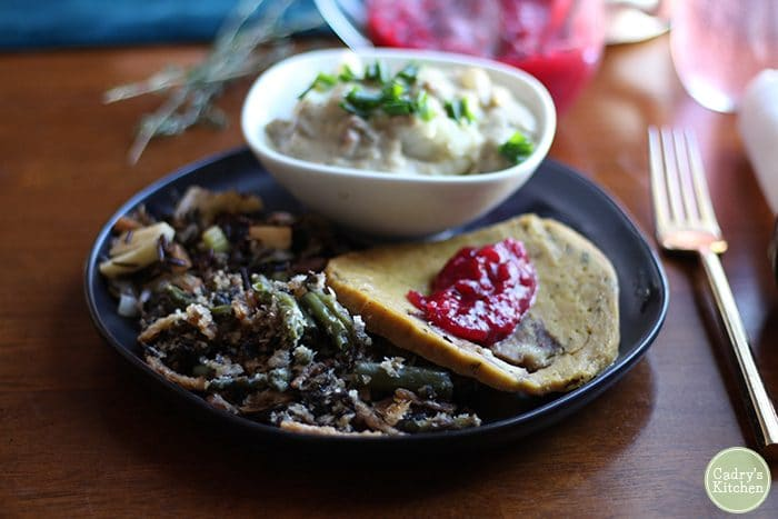 Thanksgiving plate with Herbivorous Butcher seitan, green bean casserole, mashed potatoes, and orange cranberry sauce.