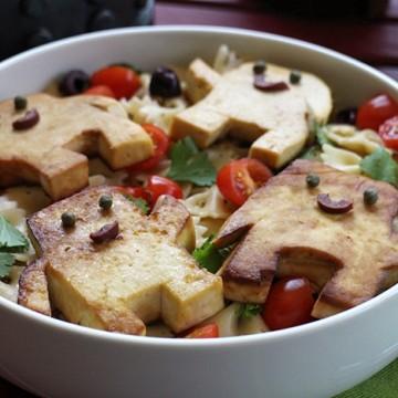 Adipose shaped tofu on top of bowtie pasta salad.