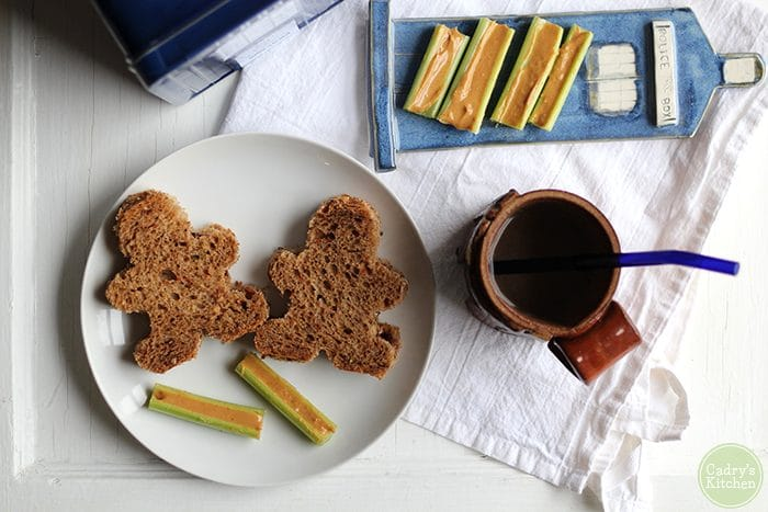 Gingerbread man-shaped peanut butter & jelly sandwiches, TARDIS plate, and mug.