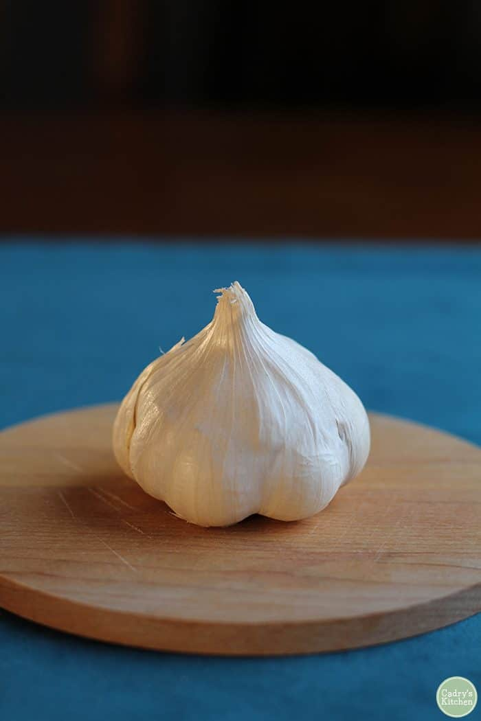 Garlic head on small cutting board.
