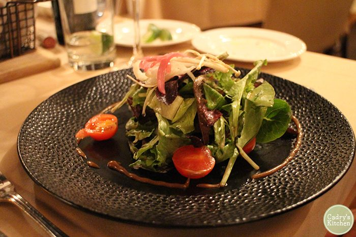 Mixed green salad with tomatoes and onions at Cedar Restaurant in Washington, D.C.