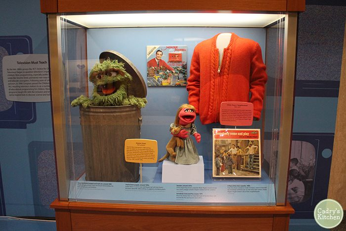 Oscar the Grouch, Prairie Dawn, and Mister Rogers' sweater at Smithsonian in display case.