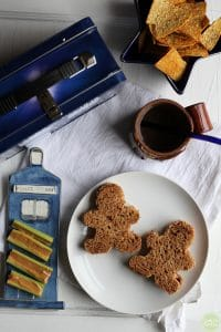 Overhead shot of peanut butter & jelly sandwiches, chips, TARDIS plate, and peanut butter celery.
