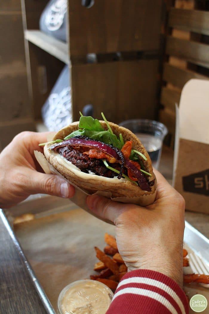 Hands holding veggie burger pita at Shouk restaurant.