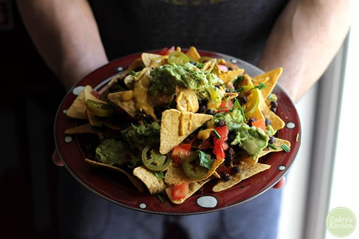 Hands holding platter of vegan nachos with cashew queso and guacamole.