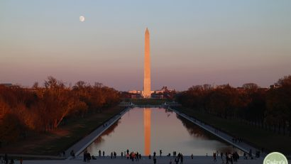 Washington Monument at sunset reflecting on water. Full moon in sky.