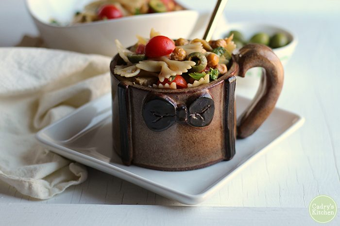 Bowtie pasta salad with cherry tomatoes and roasted chickpeas in handmade Matt Smith mug.