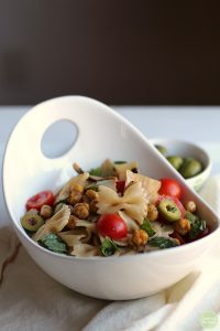 Bowtie pasta salad in white bowl with Castelvetrano olives, cherry tomatoes, basil, and roasted chickpeas.