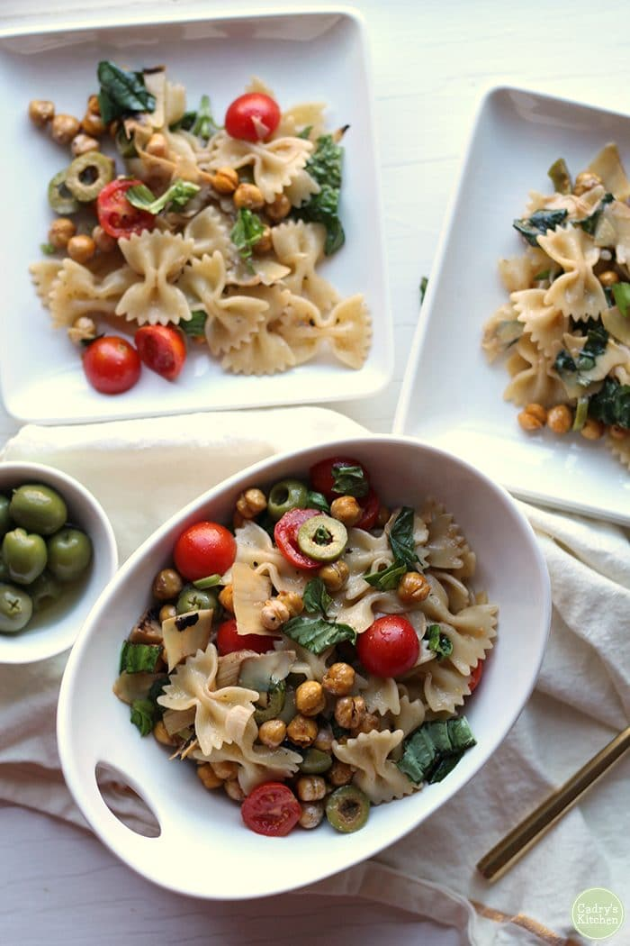 Overhead shot of bowtie pasta salad with basil, tomatoes, olives, and roasted chickpeas.