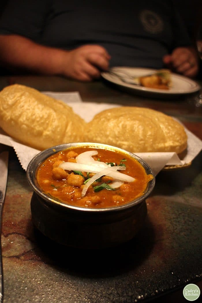 Chickpea curry in a metal bowl with poori.