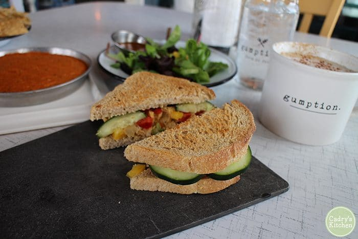 Chickpea salad sandwich with vegetables, coffee in background at Gumption.