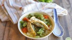 Vegetable potsticker soup in bowl by spoon.