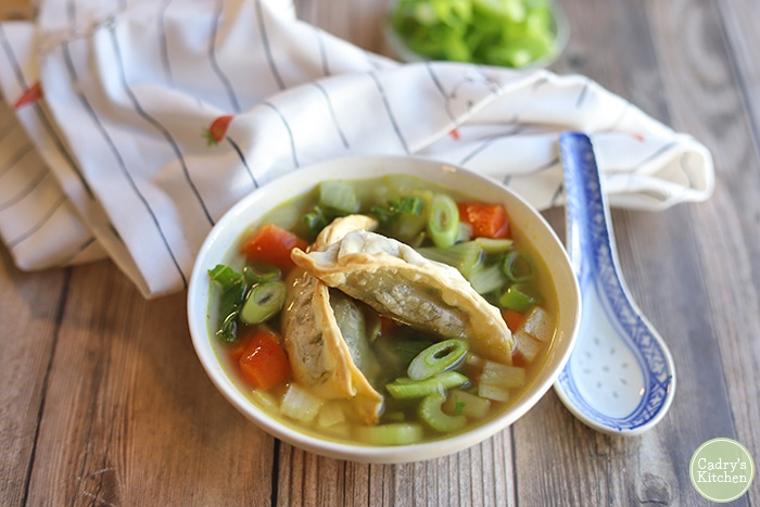 Vegetable potsticker soup in bowl by spoon.