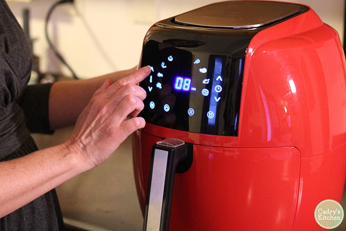 Fingers tapping display of GoWise Power XL air fryer. Vegan air fryer recipes.