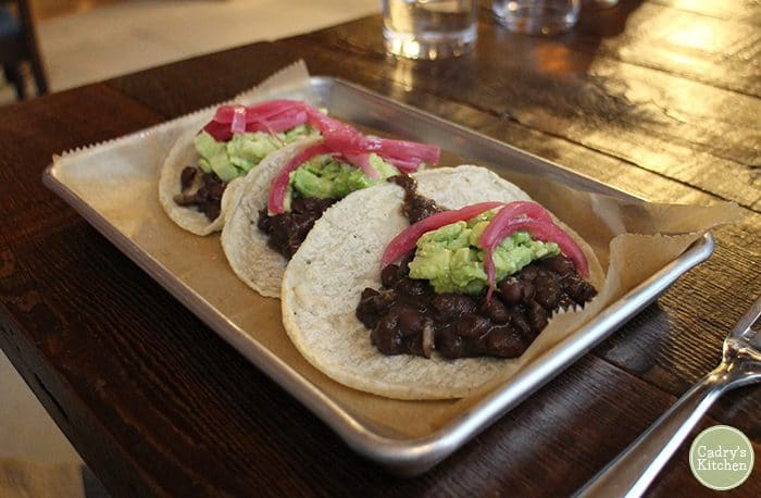 Legumbres tacos with pickled onions and guacamole at Caucho.