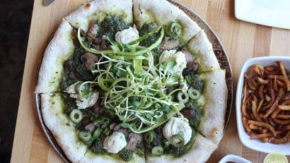 Overhead view pesto pizza with vegan cheese dollops and Castelvetrano olives at Quarter Barrel pizza.