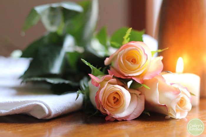 Pink tipped white roses with candle.