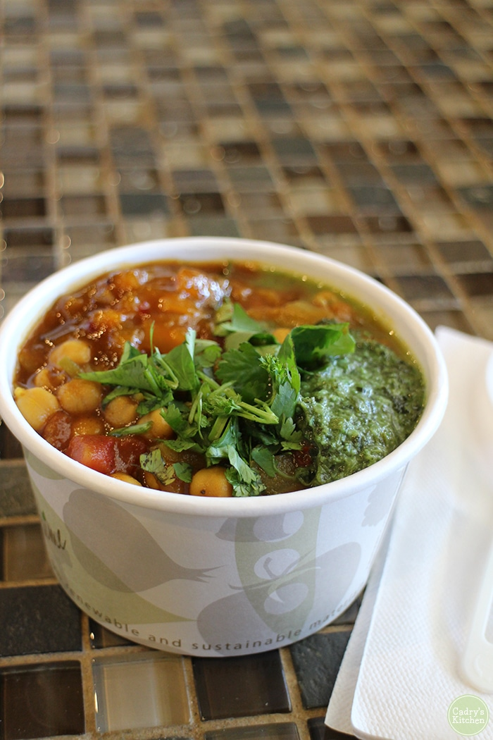 Chana masala in paper cup at The Full Bowl topped with cilantro chutney.