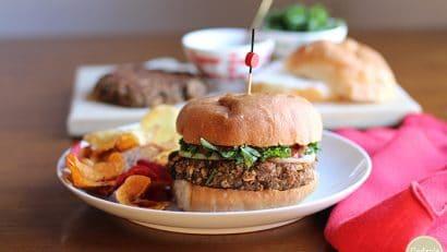 Vegan lentil burgers wiht chips, kale, and pasta sauce.