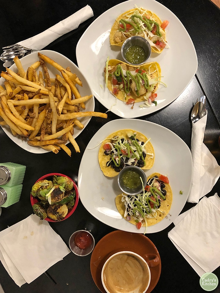 Overhead smoked cauliflower tacos, black bean tacos, fries, and Brussels sprouts at Lightworks Cafe.