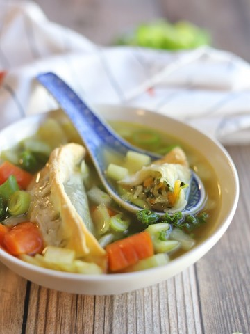 Vegetable gyoza in broth with carrots, celery, onions, garlic, and kale.