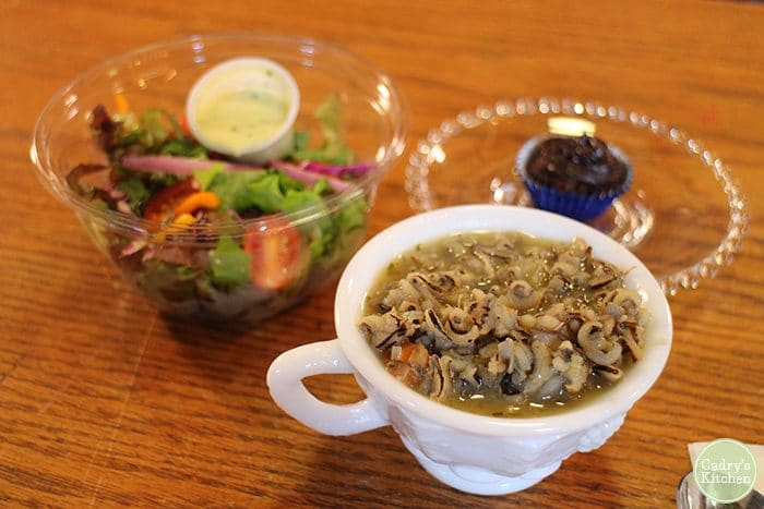 Vegetarian restaurants Cedar Rapids. Wild rice soup in mug with salad in background at Rawlicious in Cedar Rapids.