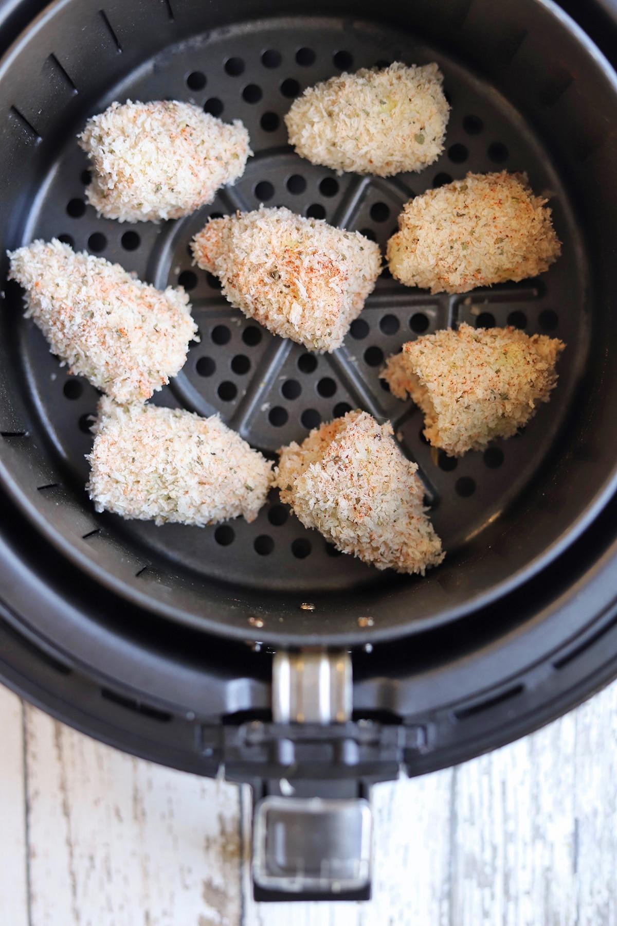 Breaded artichoke hearts in air fryer basket.