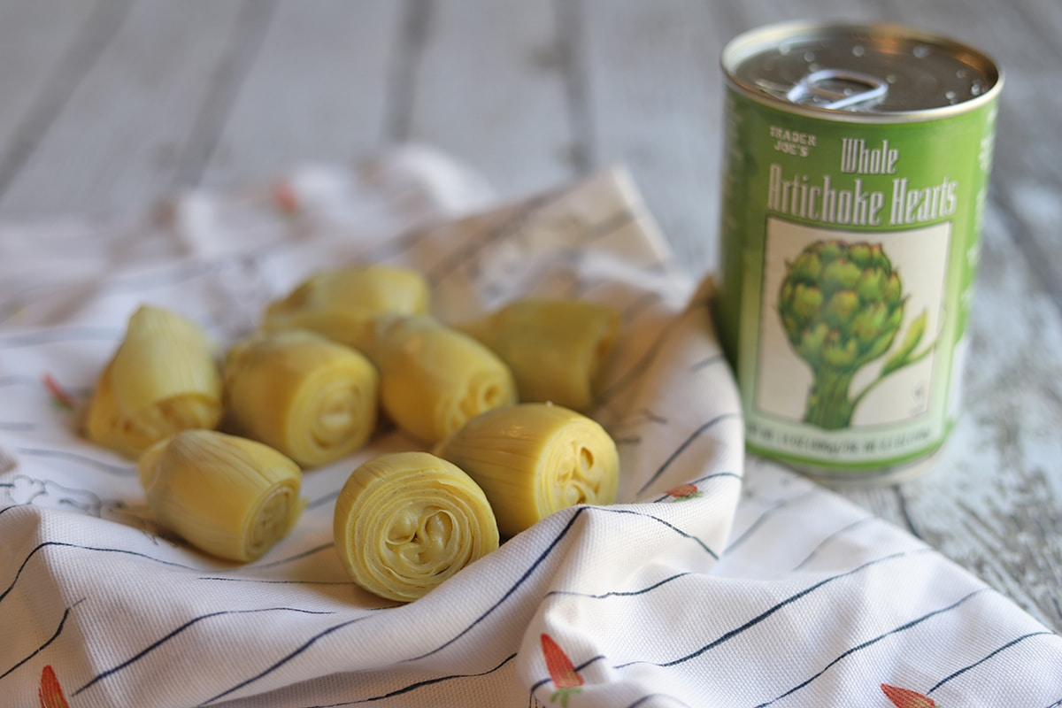 Canned artichoke hearts on towel by can.