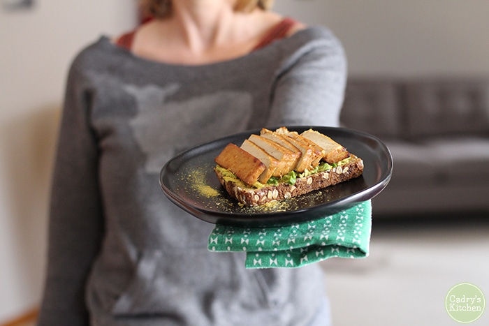 Cadry holding vegan avocado toast with teriyaki tofu on black plate. What is nutritional yeast? This post explains.