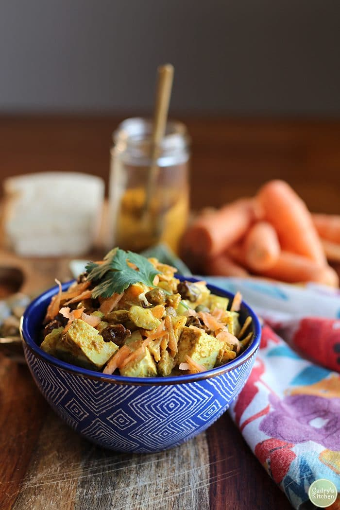 Vegan curried tofu salad in blue bowl with flower napkin.