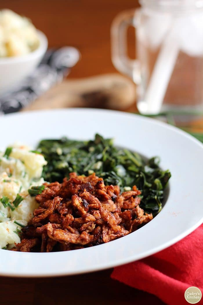 Vegan BBQ Soy Curls in a bowl with potato salad & collard greens.
