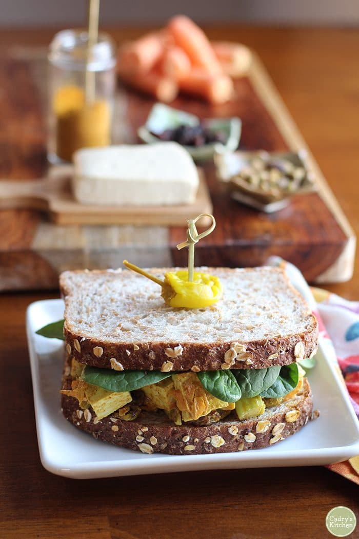 Curried tofu salad sandwich on white plate.