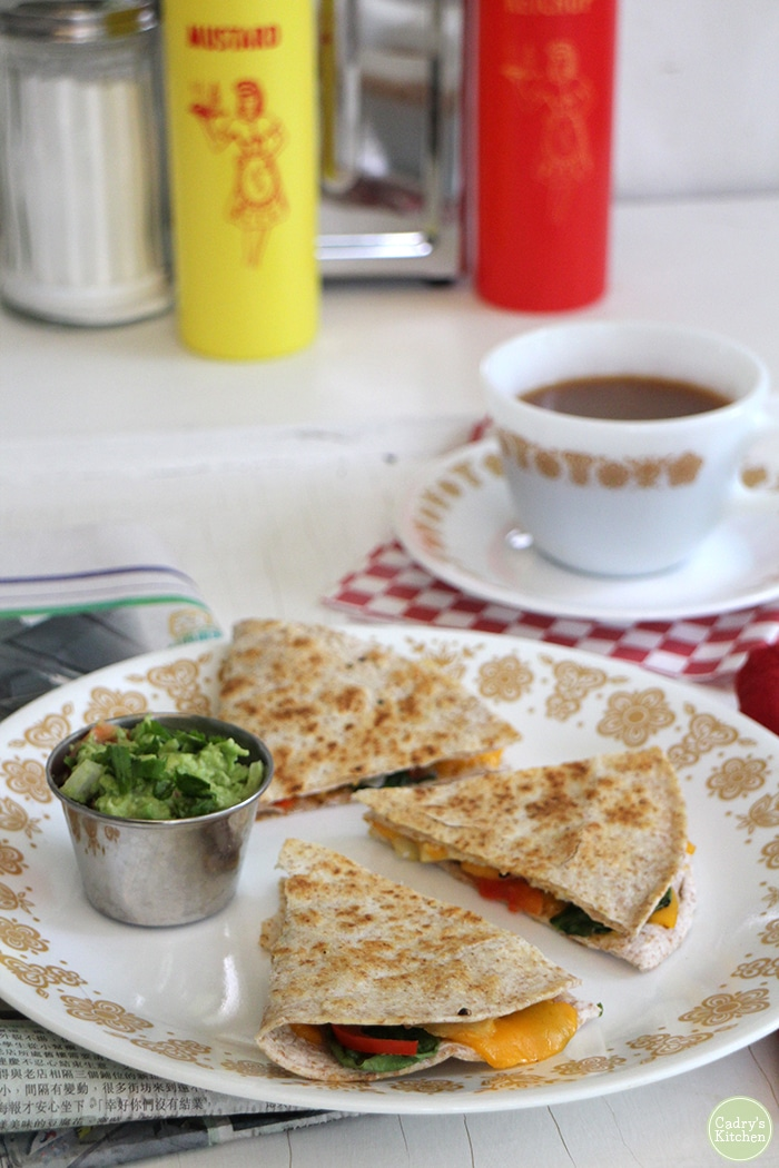 For a savory start to the day, you need this eggy tofu quesadilla. It's packed with spinach, red bell pepper, onion, non-dairy cheese, and eggy tofu. It tastes like a Denver omelette, but in vegan quesadilla form. Plus, I share how to store a cut avocado to keep it from browning. (No lemon juice involved!) #vegan #breakfast #tofu #vegetarian #brunch #quesadilla #nondairy