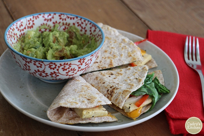 Vegan breakfast eggy tofu quesadilla with spinach, bell peppers, onions, and non-dairy cheese on plate with guacamole.