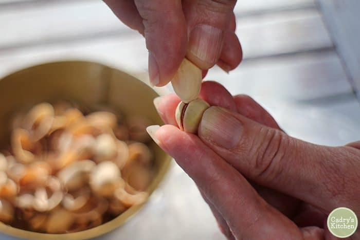 Fingers using shell to open pistachio nut.