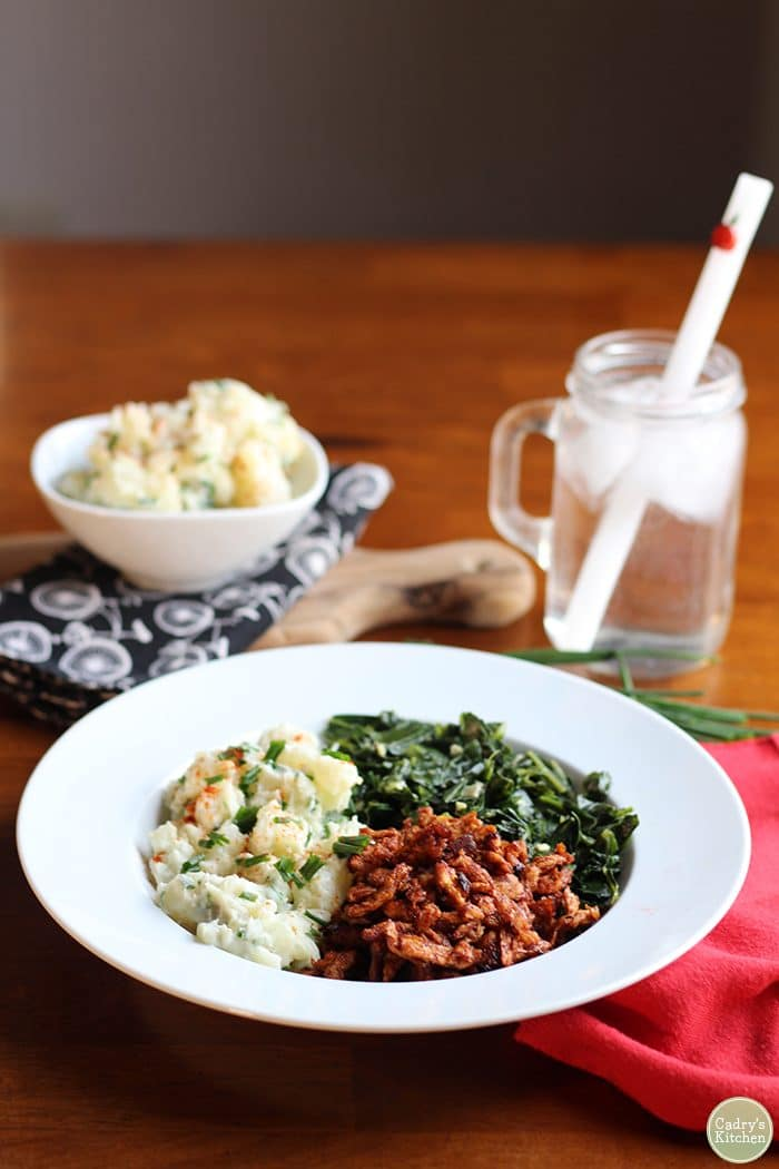 Vegan BBQ Soy Curls in a bowl with potato salad, and collard greens.