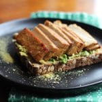 Vegan avocado toast with sprinkle of nutritional yeast flakes and teriyaki tofu on black plate.