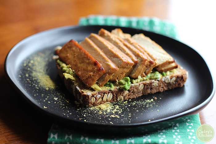 Vegan avocado toast with sprinkle of nutritional yeast flakes and teriyaki tofu on black plate.