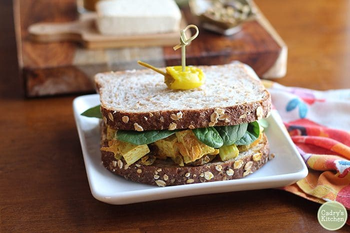 Curried tofu salad sandwich with pepperoncini on plate.
