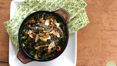 Overhead picture of vegan lentil recipe with caramelized onions and pistachios over cooked kale in small casserole dish.