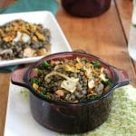Purple bowl filled with French lentils du Puy, caramelized onions, and pistachios over kale.