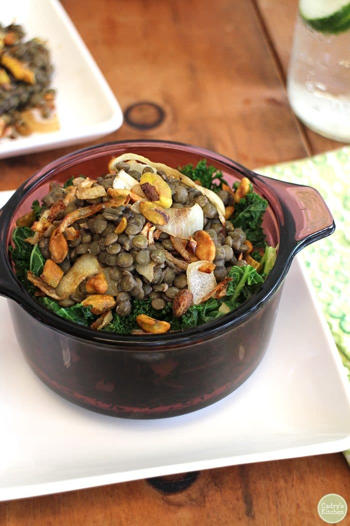 Close-up lentils in purple dish with caramelized onions and pistachios over sauteed kale in purple dish.