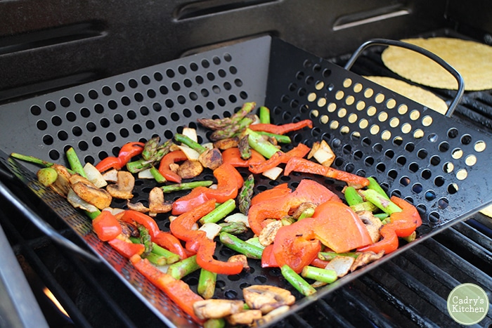 Peppers, onions, asparagus, and mushrooms in grill basket.