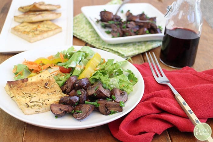 Red wine mushrooms on plate with lemon rosemary tofu, and salad. Bottle of red wine in background.