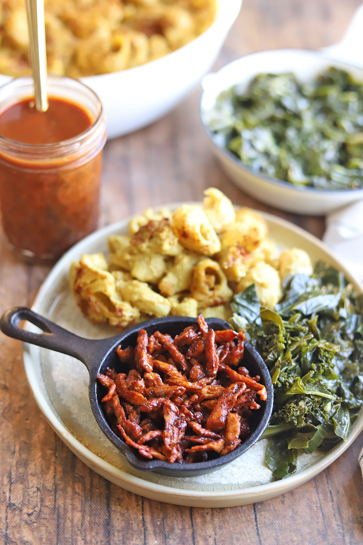 Barbecued Soy Curls on plate with collard greens & non-dairy mac & cheese.