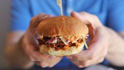Hands holding vegan BBQ sandwich with coleslaw.